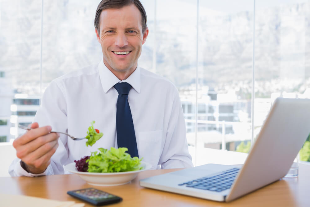 Happy businessman eating a salad on his desk during the lunch time (1)